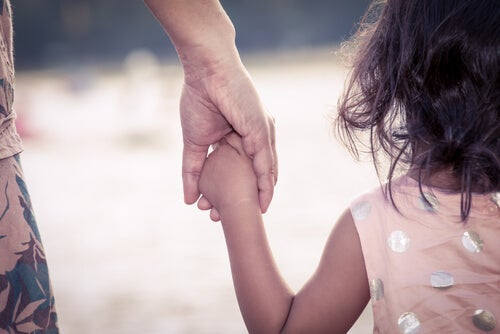 A child holding an adult's hand.