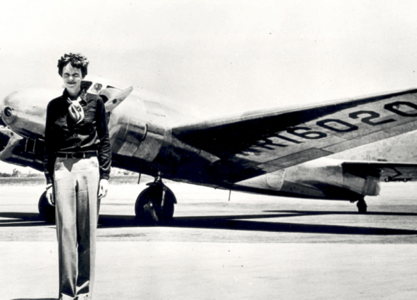 A picture of Amelia Earhart in front of plane.