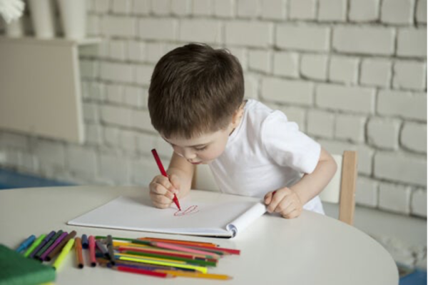 A boy drawing, showing the importance of children's drawings in their world.