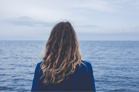 A woman looking out at the ocean living a meaningful life.