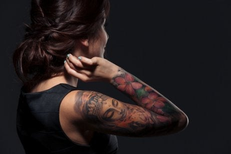A woman showing her arm tattoos.