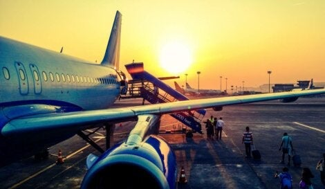 People boarding a plane at sunset.