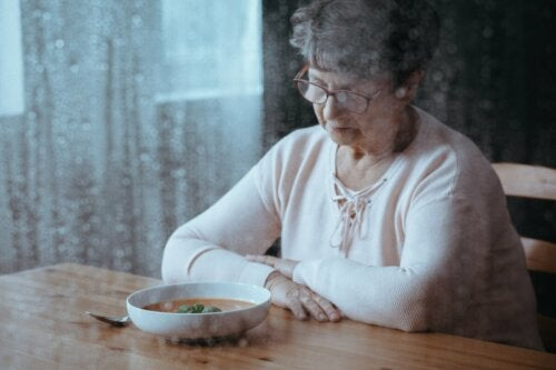 An elderly woman feeling sad looking at a plate of food.