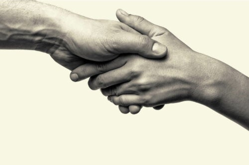 Two people holding hands, representing prosocial behaviors.