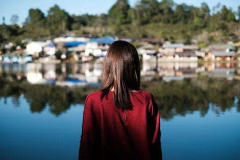 A woman looking across a lake towards a small village.
