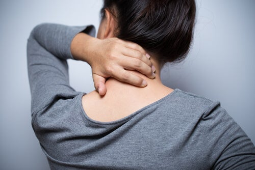 A woman rubbing her neck.
