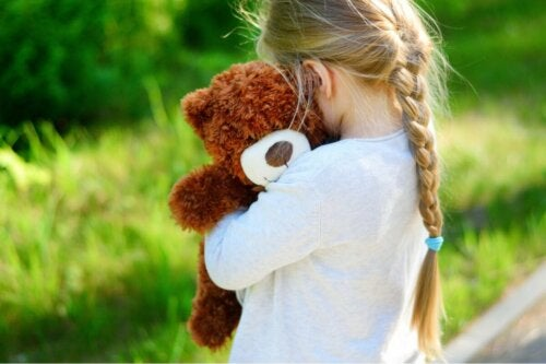 A girl hugging her teddy bear.