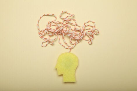 A cutout of a head with a string illustrating thought.