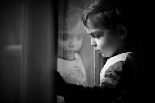 A sad child looking out the window.