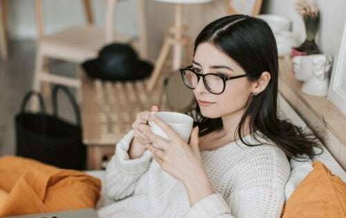 A woman wearing glasses drinking coffee.