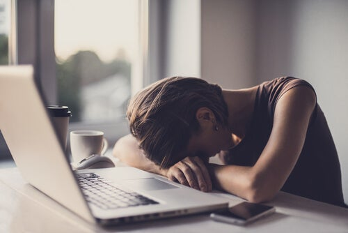 A woman sleeping at her desk.