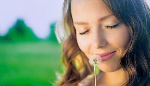 A woman sniffing a dandelion.