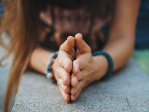 A woman with hands clasped.