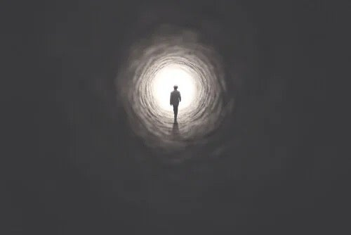 A figure walking into a tunnel.