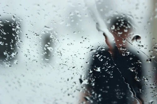 A figure seen through a rainy window.