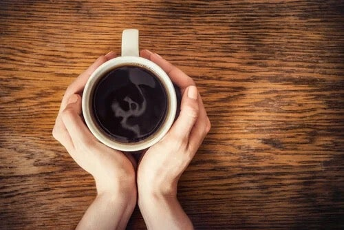 Hands around a cup of coffee.