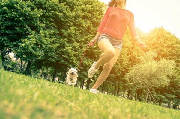 A woman walking a dog.