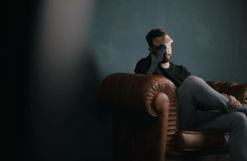 A worried man sitting on a couch.