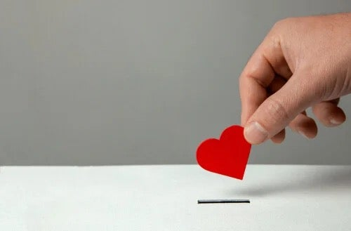 A red heart being put in a box.