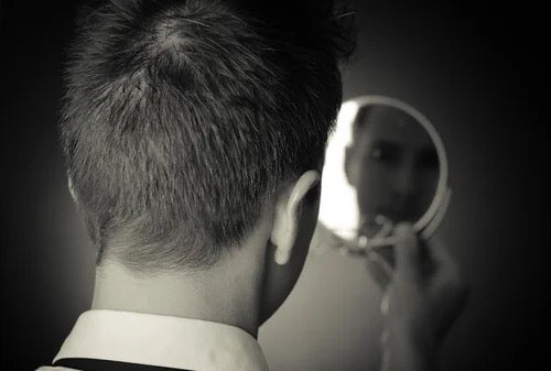A man looking in the mirror.