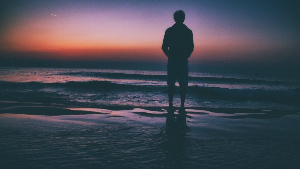 A person standing at the sea shore.