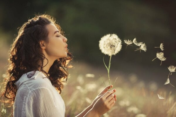 A woman blowing a dandelion.