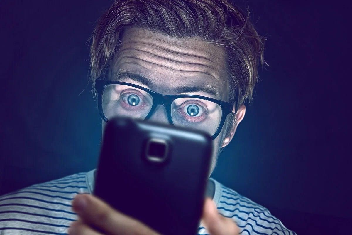 A man looking at a phone exhibiting morbid curiosity.