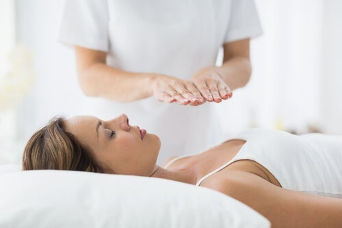 Woman lying down with another person givin therapuetic touch.