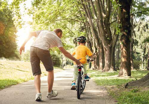 A man teaching a child to bike.