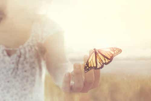 A woman touching a butterfly.