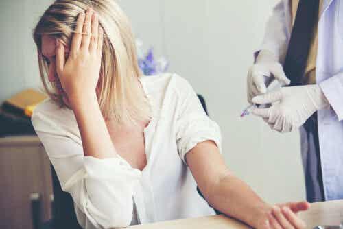 En kvinde ser bort fra en blodprøve på grund af nålefobi
