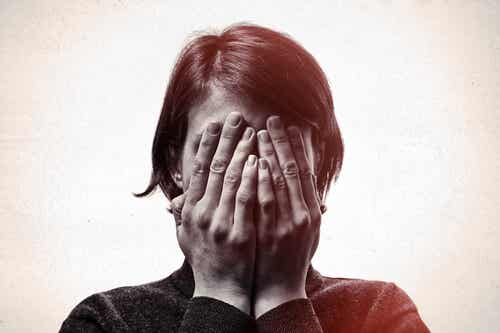 A woman hiding her eyes because of belonephobia.