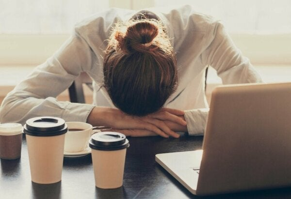 Exhausted woman with her head on the table showing what lies behind laziness.