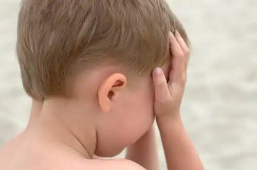 A child with his face in his hands showing childhood anxiety.