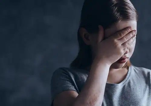A distressed girl, maybe experiencing social rejection.
