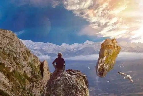 A man sitting on a rock thinking maybe about changing his limiting beliefs.