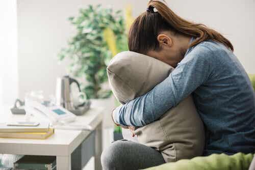 Kvinde, der gemmer hoved i pude, oplever træthed på arbejdet
