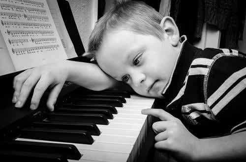 Poika istuu pianon luona.