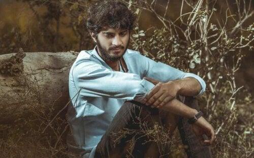 Mężczyzna siedzący samotnie w lesie.