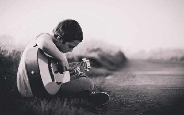 A sad boy playing a guitar.