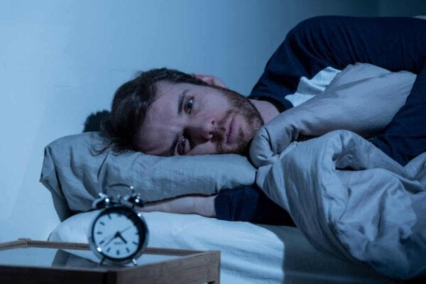 An image of a stressed out man in bed.