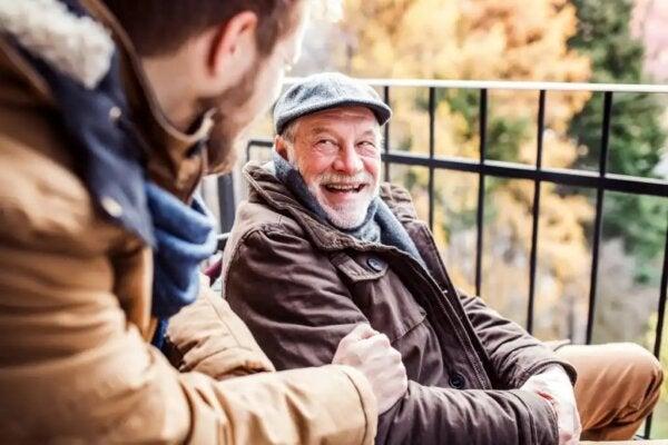 An elderly man laughing.