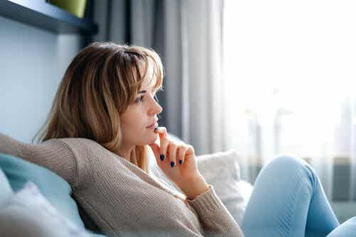 An image of woman on sofa holding her chin.