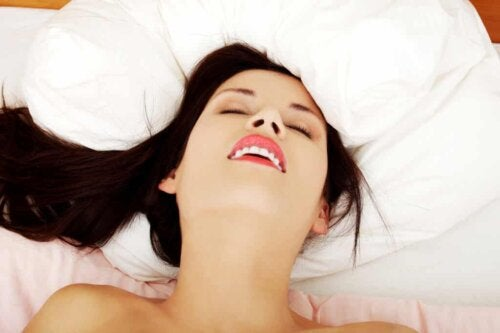 A woman smiling in bed.