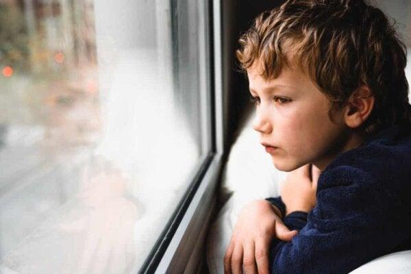 Trist barn ser ud af vindue