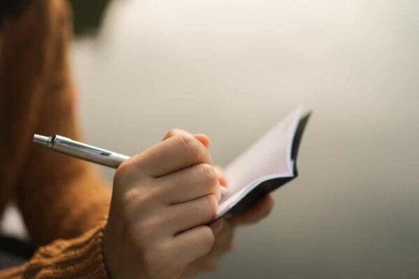 En person som skriver i en bok.
