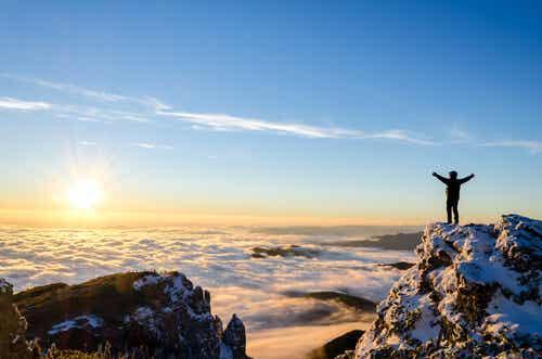 Bir dağda başarısını kutlayan bir adam.