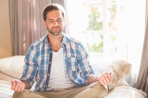 En man som mediterar i sängen.