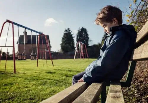 A child sitting on a bench, maybe a school dropout.